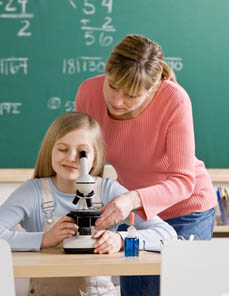 Teacher helping student adjust microscope in school science classroom